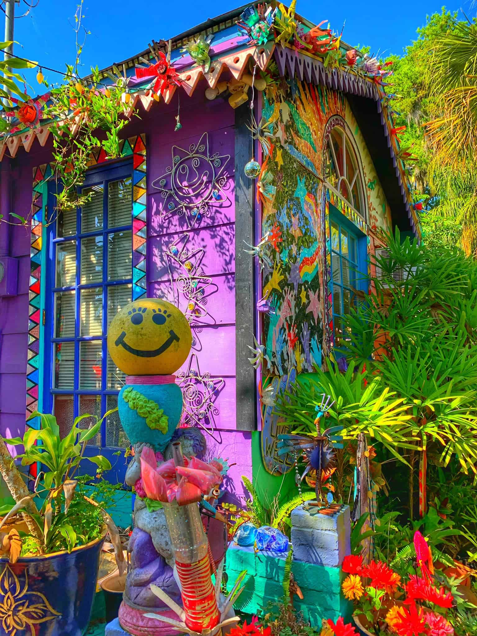Corner of Whimzeyland house, with smiley face bowling balls, brightly colored sculptures and pieces adorn the home as well as the surrounding space outside