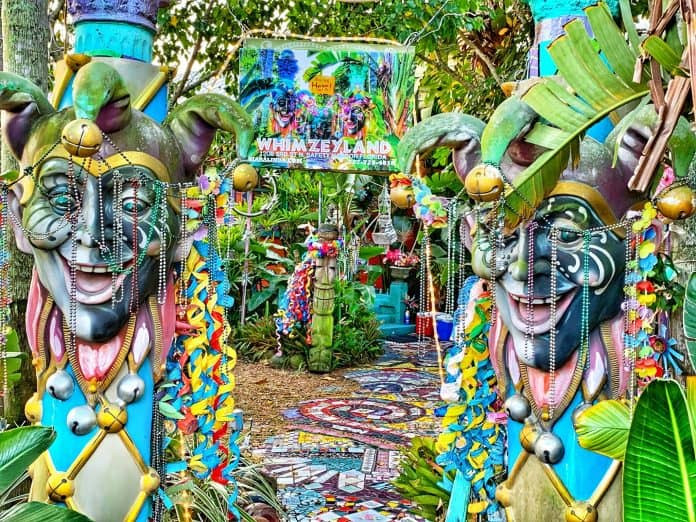 Ourdoor pathway into Whimzeyland property. Giant mardi gras masks, colorful tiles, beads, and sculptures