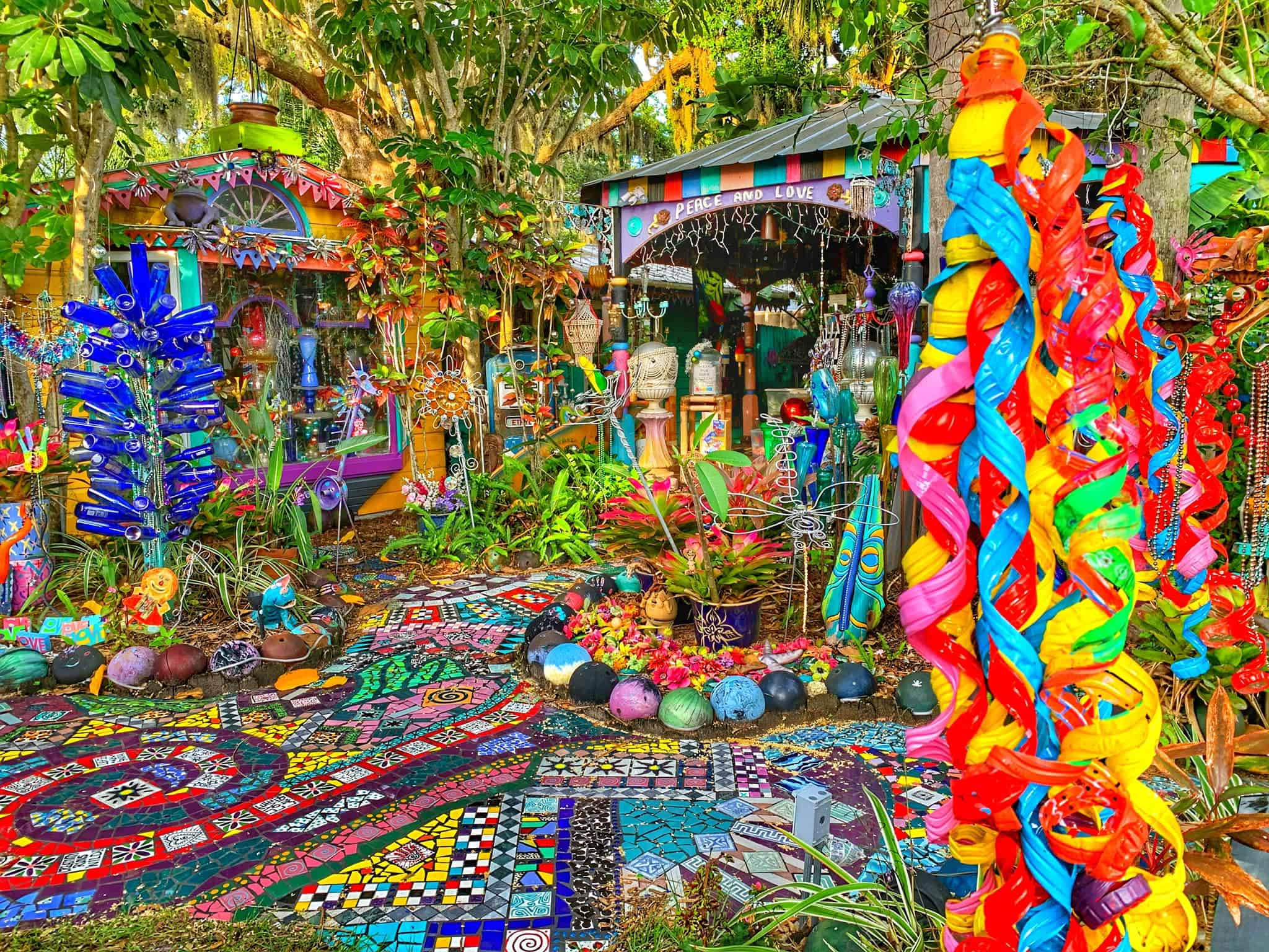 Outdoor portion of Whimzeyland. Brightly colored tiles make a swirl path, lots of ornate sculptures, bowling balls, and other piece hang from trees and are covering the ground