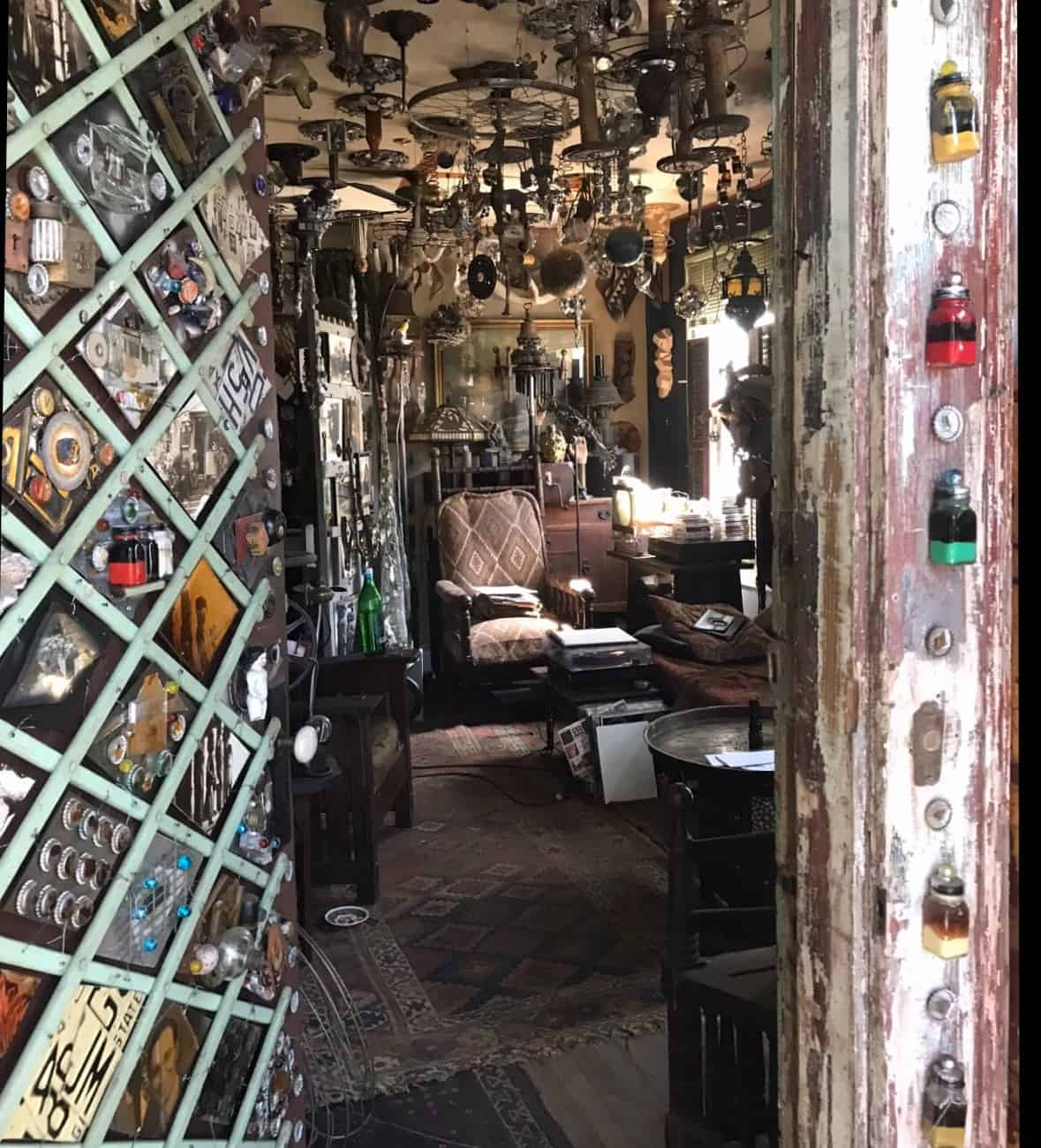 Inside a room of the art house, the walls and ceiling are covered with pieces of metal, glass, and other things