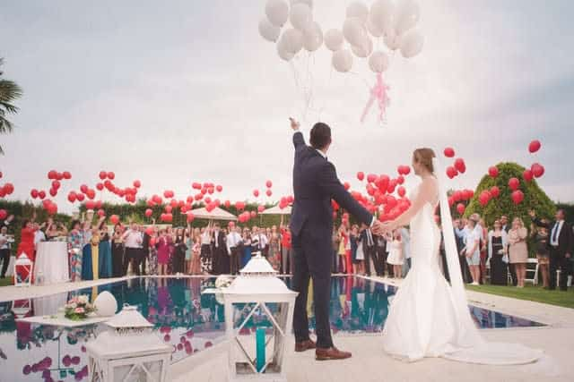 Outdoor wedding ceremony, releasing red balloons