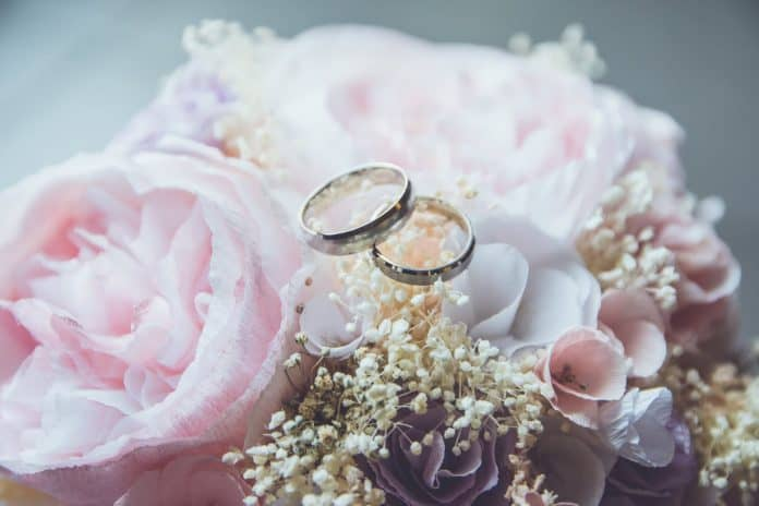 Pink rose bouquet with wedding rings set on top