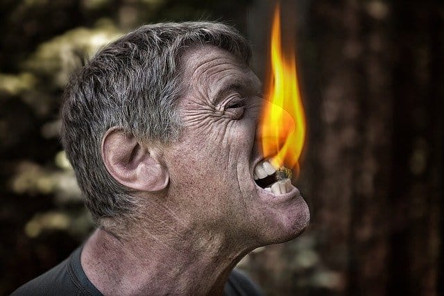 Man straining his neck, with something in between his teeth, and a small flame coming from this thing in his teeth