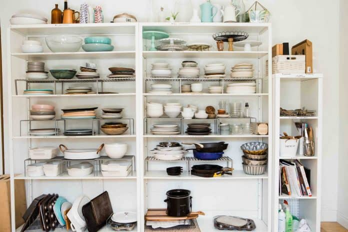 Two large open kitchen pantry shelves, full of plates, bowls, pots, and pans