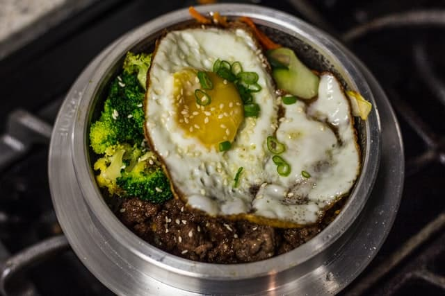 Bowl of bibimbap, with an egg, broccoli, and beef visible on top of the rice