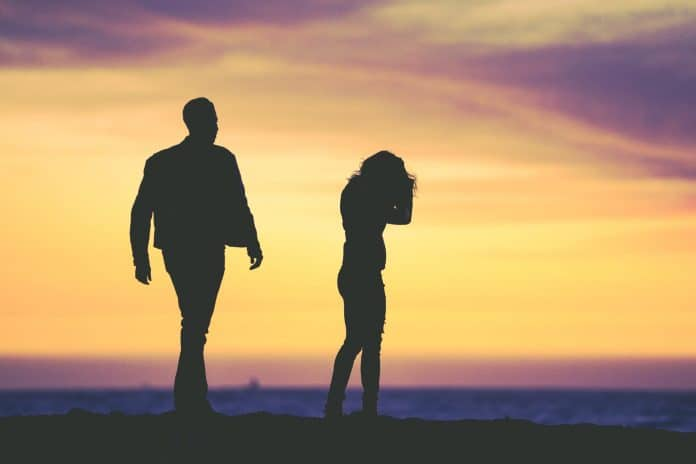 Couple in distress on beach at sunset