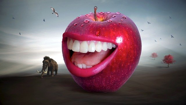 A red apple with a human smiling mouth in its center, set on the ground next to a woolly mammoth, all among rolling hills with two trees in the background