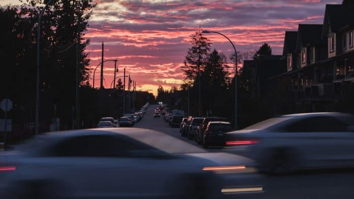 Sunset view from a busy city intersection, with cars blurry driving by