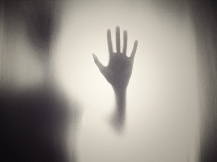 Scary hand behind window, blurry and foggy