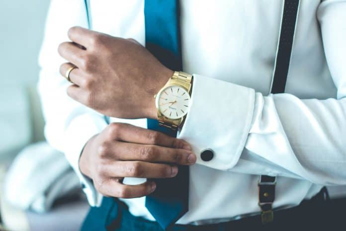 Man standing with nice clothes on, fixing cuff, with nice watch on wrist