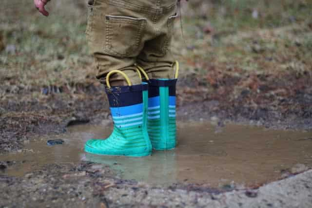 Kid wearing rain boots, standing in a muddy puddle
