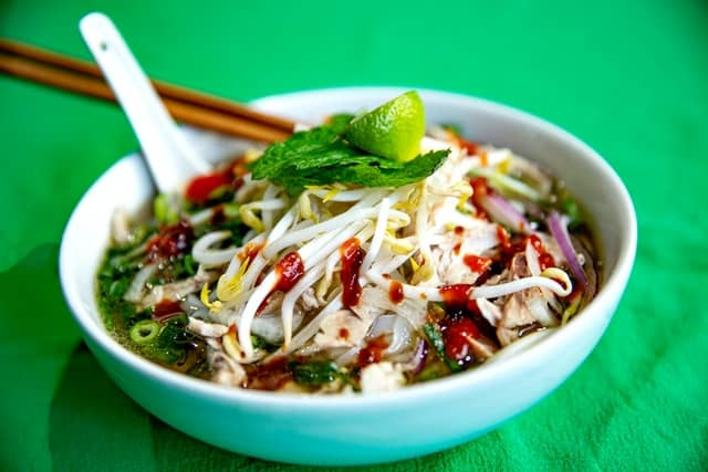 Bowl of pho, covered with bean sprouts, basil, and a lime wedge