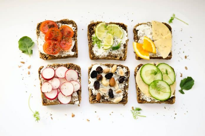 Six pieces of toast lined up, each with different fruits, veggies, or spreads on them