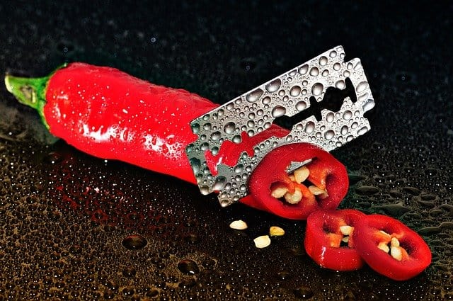 Red chili pepper covered in water droplet, being sliced with a razor blade