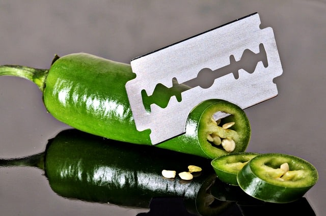 Green jalapeno being sliced with a razor blade, and it's reflection seen on the table underneath