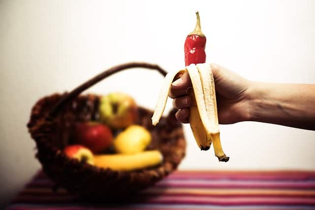 Hand holding a peeled banana, instead of the fruit the top of a hot pepper in in the peel