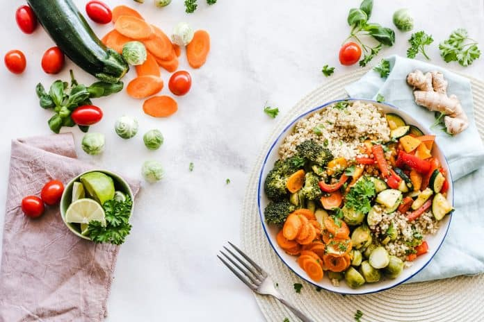 Dinner plate filled with vegetables and quinoa, on a table with more veggies surrounding