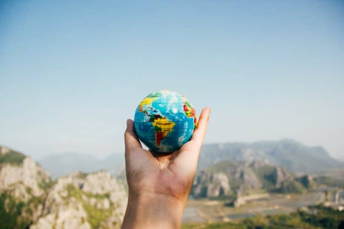 Hand holding up a small toy globe in front of a mountain range