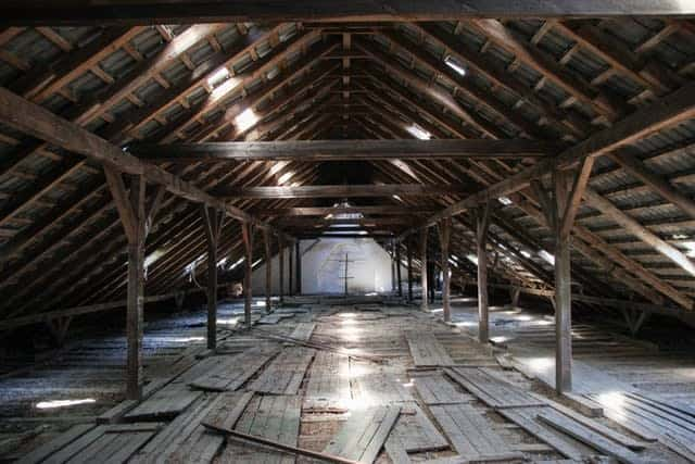 Large, wooden attic with dust and debris