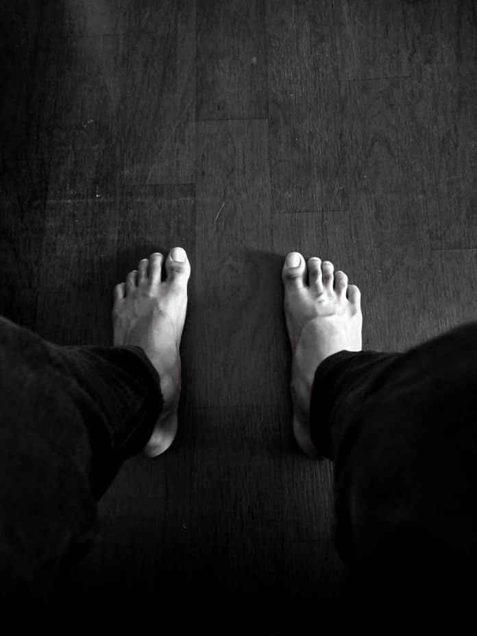 Black and white photo of top of feet flat on floor