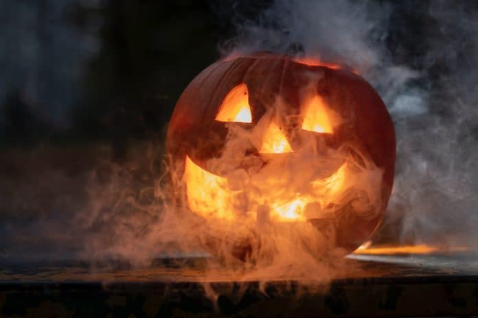 Jack-o-lantern carved with smiling mouth, smoke coming out of it, backlit by a candle inside the pumpkin