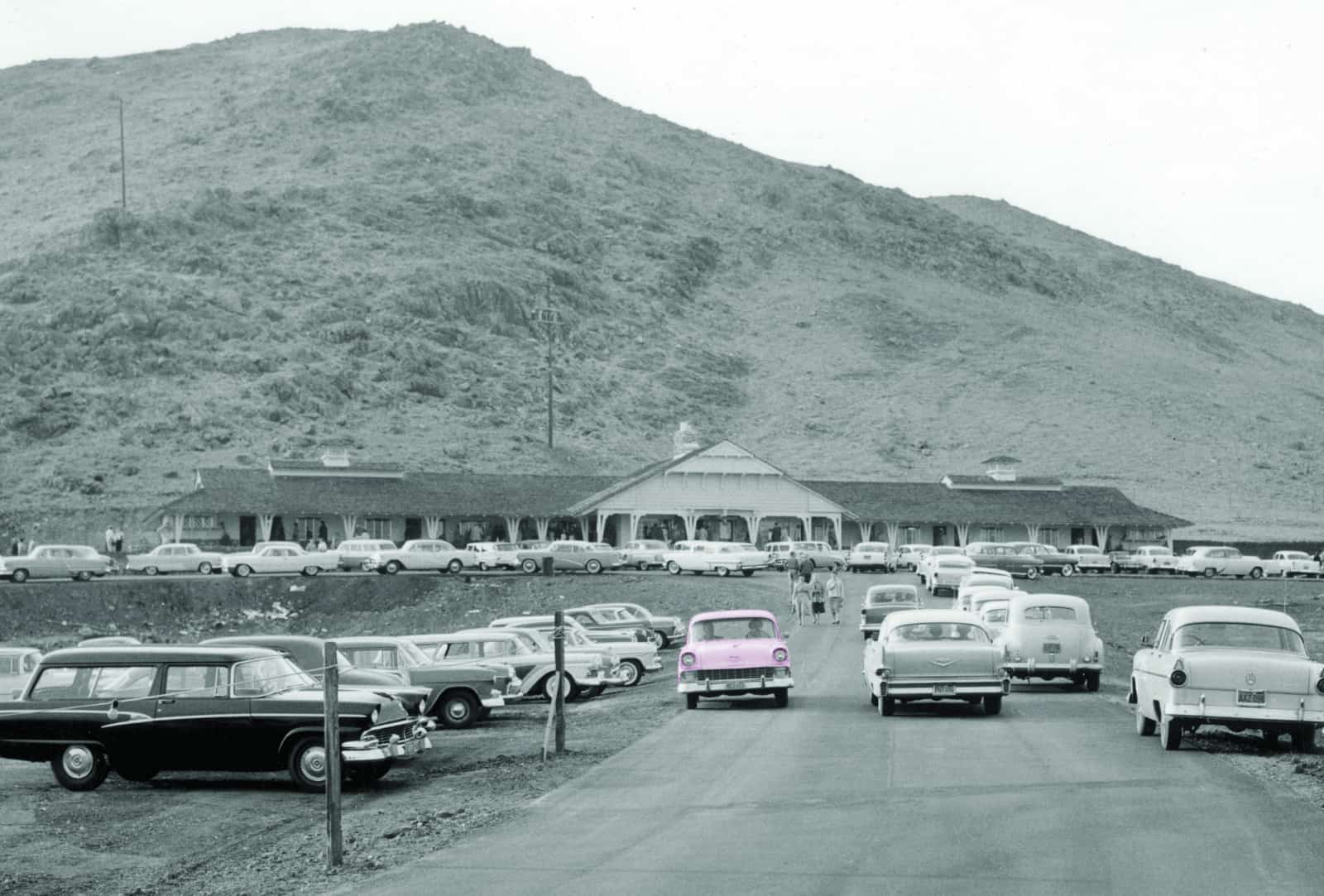 Vintage shot of the Inn, much smaller, with 1950s cars in the parking lot