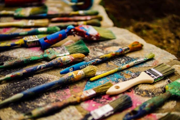 Two rows of paint brushes, covered in old paint