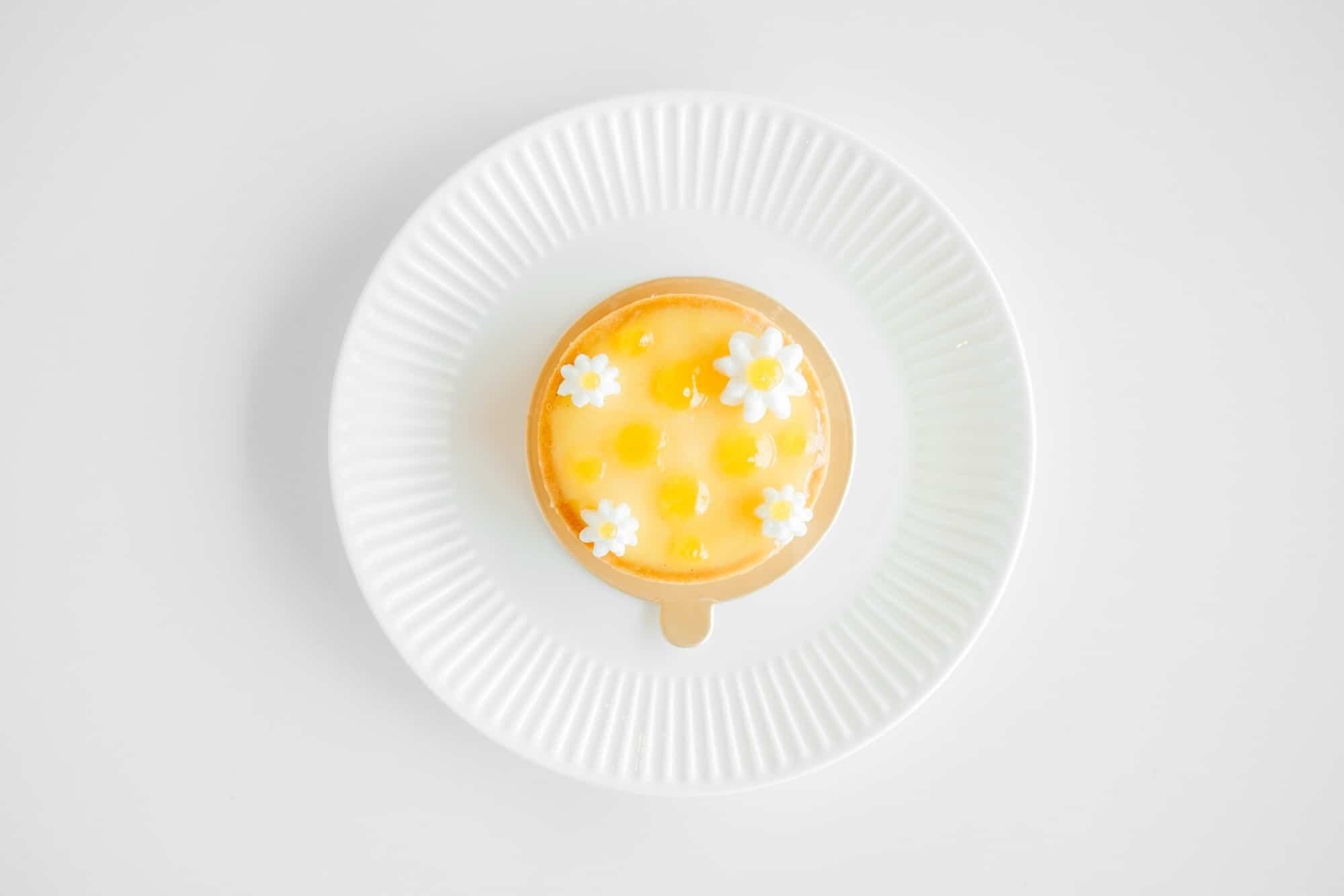 White plate with yellow pudding dessert in center