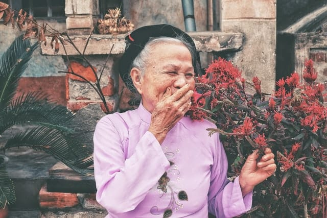 Older woman dressed up nicely, laughing outside