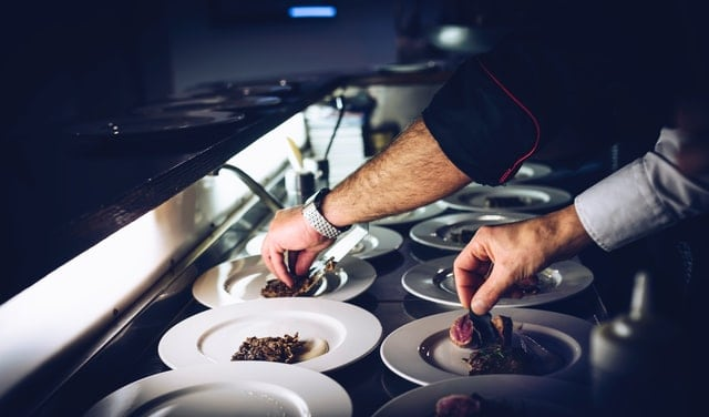 Chef prepping plates in kitchen