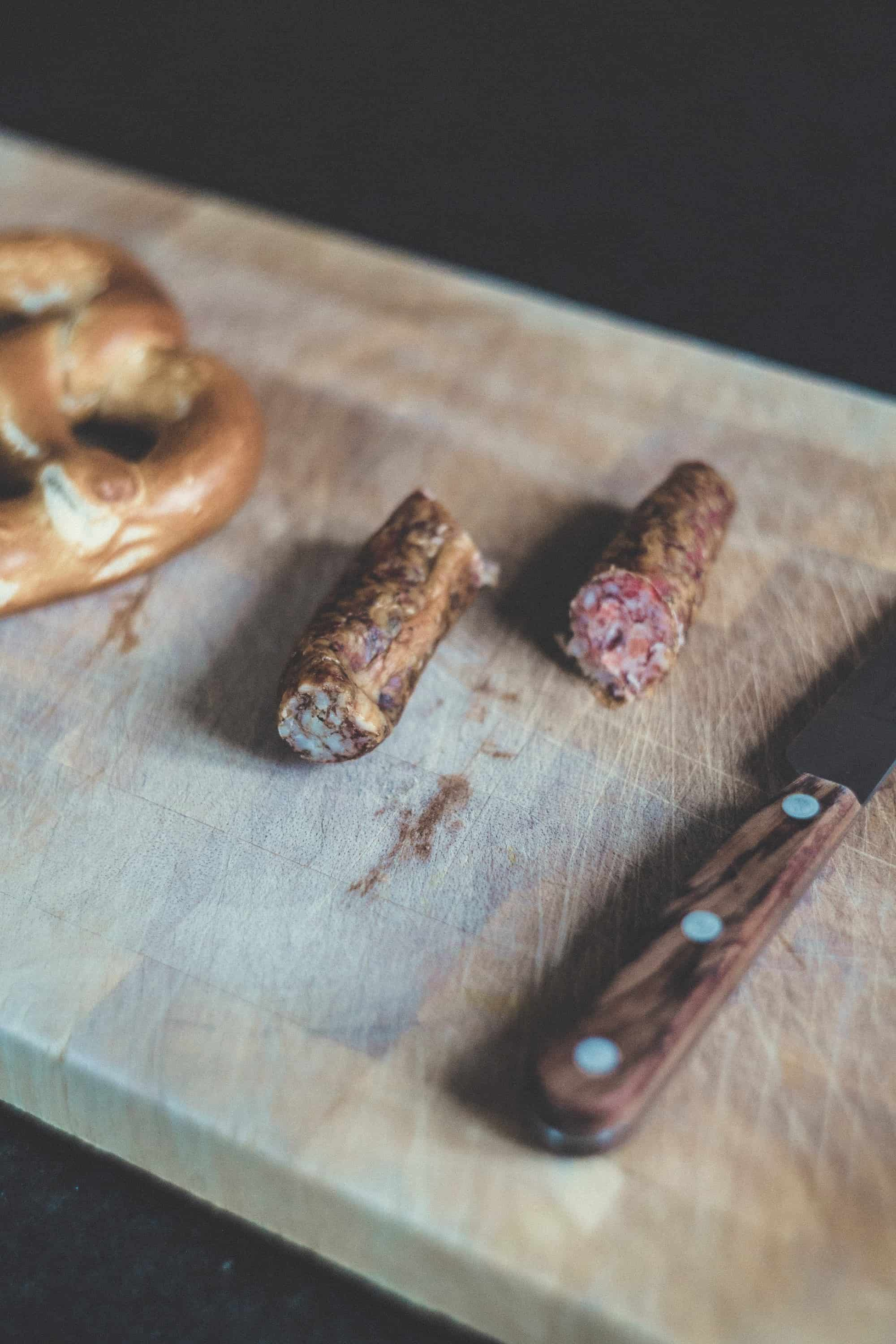 Wooden cutting board with part of a pretzel and sausage cut in half on it